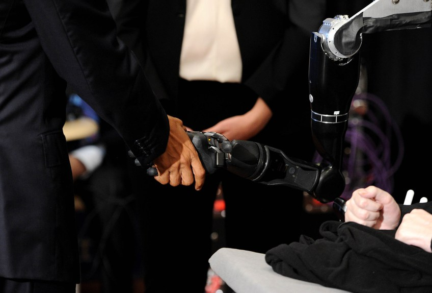 President Barack Obama shakes hands and fist bumps with a robotic arm controlled by the mind of Nathan Copeland, at right, in the exhibition hall of The White House Frontiers Conference at the University of Pittsburgh on Thursday, Oct. 13, 2016. Copeland is a quadriplegic with a brain implant that can allow him to control the remote arm and experience the sensation of touch through it. (Photo by Michael Henninger/Post-Gazette)