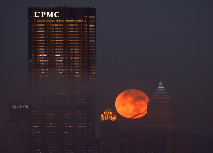 The moon sets between the the Koppers Building and the Gulf Tower with the US Steel Tower to the left Monday morning Nov. 14, 2016. The photo was taken at 6:45 a.m. (Darrell Sapp/Post-Gazette)