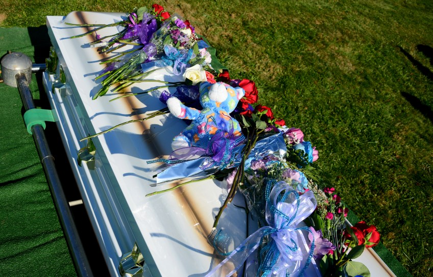 A Teddy bear and flowers are laid on the coffin of Dalia Sabae.