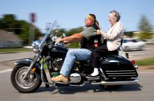 Irene Morar grips the back of Michael Kopera's, of Evan City, leather vest while riding on a motorcycle on Sunday, Sept. 10, 2017 at the Lutheran Senior Life Passavant Community in Zelienople. Caretakers at the Lutheran Senior Life Passavant Community wanted to fulfill Alvin Graf's, 98 years old, wish of riding a motorcycle after not having ridden one since WWII. The American Legion Riders offered their help and came out to not only grant Graf's wish, but also other senior residents who got the opportunity to go out on a joyride. (Antonella Crescimbeni/Post-Gazette)