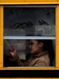 A girl draws with the condensation on a school bus window on Friday, March 31, 2017 while riding along Penn Avenue in East Liberty. (Steph Chambers/Post-Gazette)