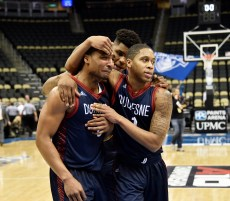 Emile Blackman, gets comforted by teammates Nakye Sanders, center, and Mike Lewis II, after Duquesne loses to St. Louis 72-70 during the first round of the Atlantic 10 Tournament Wednesday, March 8, 2017, at PPG Paints Arena in Uptown, Pittsburgh. (Rebecca Droke/Post-Gazette)