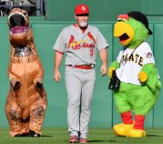 Cardinals Jedd Gyorko walks between a dinosaur and the Pirate Parrot before taking on the Pirates Saturday, July 15, 2017 at PNC Park in Pittsburgh. (Matt Freed/Post-Gazette)