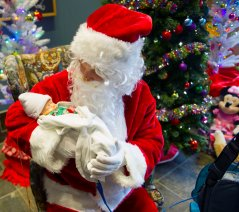 Santa, portrayed by a member of the University of Pittsburgh Imagination Project, holds 21-day-old Bentley Sakel of Beallsville on Sunday, Dec. 10, 2017, at the The ChildrenÕs Home of Pittsburgh & Lemieux Family Center. The Jerome Bettis Bus Stops Here Foundation and Pitt Vets Team Up to Donate ÒA Bus FullÓ of Christmas Gifts to The ChildrenÕs Home of Pittsburgh & Lemieux Family Center. (Nate Guidry/Post-Gazette)