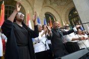 """The Rev. Deryck Tines, center, and the Lemington Gospel Choir lead a crowd in singing """"Lean on Me"""" at the Prayer for Pittsburgh, Prayer for Peace gathering in front of the City-County Building on Friday, August 18, 2017. At left is choir member Donna Lowery. (Steve Mellon/Post-Gazette)"""