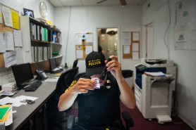 Officer Jake Alex inspects confiscated stamp bags as he does paperwork at the end of his shift on Aug. 17, 2017 at the Mt. Oliver Police Department. (Stephanie Strasburg/Post-Gazette)