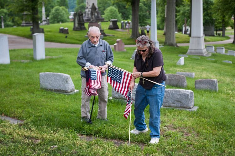 """Event organizers Marlene Scholze, right, 58, and World War II veteran Pietro Fantone, 94, both of Bloomfield, volunteer to place American flags at the graves of veterans on Monday, May 21, 2018, in preparation for Memorial Day at Allegheny Cemetery in Lawrenceville. """"I have tears in my eyes every time I come here,"""" said Fantone, who has been coming to volunteer to place flags at the graves of veterans for 69 years. (Stephanie Strasburg/Post-Gazette)"""
