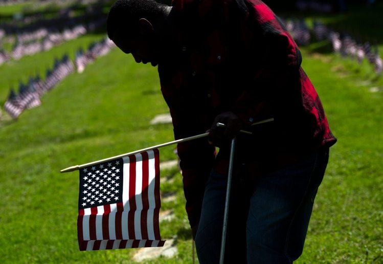 Cahlil Duckett, 25, of East Liberty places flags on the graves of military veterans with Pittsburgh Mercy Intellectual Disabilities Services on Wednesday, May 22, 2018, at Allegheny Cemetery in Lawrenceville. (Steph Chambers/Post-Gazette)