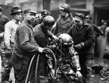 Diver putting on suit to go down and turn off main lines (The Pittsburgh Press photo)