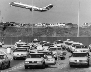 Yellow Cabs wait their turn for a fare in the taxi holding area of the Pittsburgh International Airport as a USAir flight takes off (Oct, 1994). John Beale/Post-Gazette