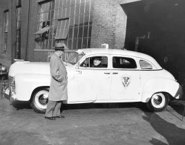 Mayor David Lawrence inspects the new Yellow cab with the head of Yellow Cab Co. (Nov., 1948)