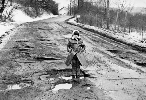 "A young girl discovered potholes made excellent ""wading ponds"" on Babcock Boulevard in Pine Township. (Pittsburgh Press photo)"