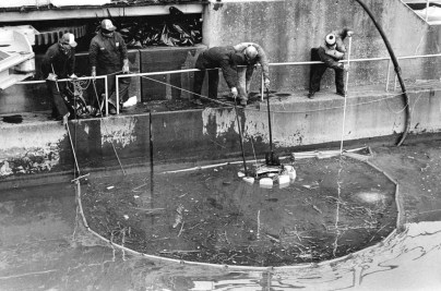Workers at Braddock Lock pump oil from the river (Tony Tye/Post-Gazette)