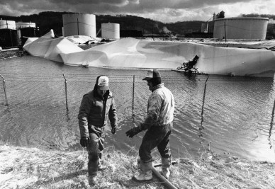 Two workers of the pumping crew place a hose in the pool of diesel fuel at the Ashland site (Darrell Sapp/Post-Gazette)