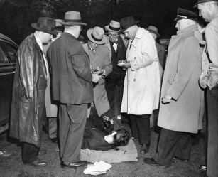 Detectives examine the body of Evans. (Pittsburgh Press photo)