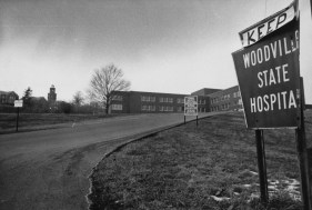 Feb. 10, 1983: Woodville State Hospital sign and driveway, with a plea for its continued existence. The facility would not close for another eight years after this image. (Mark Murphy/Post-Gazette)