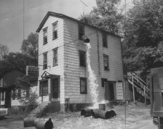 June 7, 1958: Authorities dump a giant moonshine cocktail out the window of the former Cinderella Gardens in Millvale. (The Pittsburgh Press)