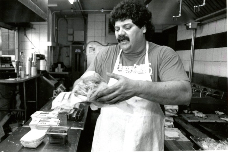 Rondey Oliviero of Primanti Bros. serves up famous cheesesteak sandwiches complete with fries and coleslaw at Three Rivers Stadium, 1994, Martha Rial/Post-Gazette