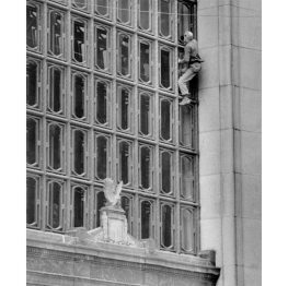 A window washer at the Post-Office Building on Grant Street climbs outside to clean windows. (Post-Gazette photo)