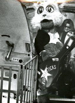 Fiddlesticks, the Pittsburgh Symphony mascot, exits a U.S. Air plane at Pittsburgh Intl Airport with Susan McClain , his creator. McClain has arrived from New York for the mascot's unveiling, 1992, Post-Gazette photo.