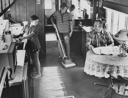 Cindy Volkwein,age 11, at left, and her sister, Terry Volkwein, 14 , help their father, George, keep their floating houseboat clean.