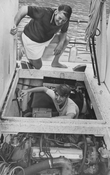 This 1970 image shows Leo Tyler and his son, Lee, below, working on the houseboat's motor.