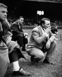 This is a typical Buddy Parker pose -- squatting on the sidelines. This picture was made  when Parker was a coach in Detroit in 1953. (The Detroit News)