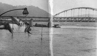 In June 1972, a band of spectators moved to the railing to view the rising Allegheny River as it advanced on downtown, covering the 10th Street Bypass at left in this picture and a ramp leading to the Fort Duquesne Bridge. (Stewart Love/The Pittsburgh Press)