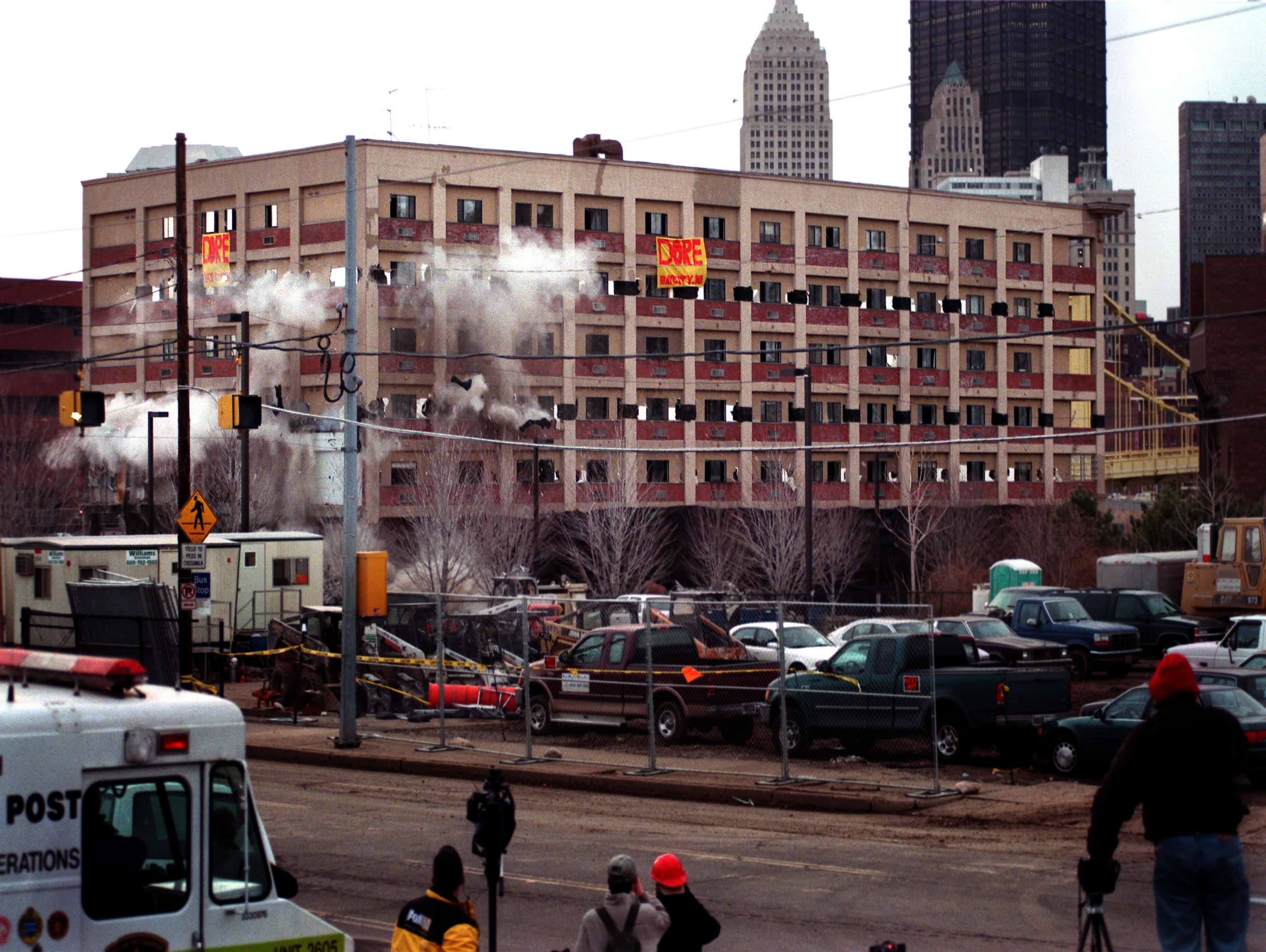 Three Rivers Plaza high rise apartment complex was imploded at 7 a.m. Watching the implosion are construction workers, invited guests and media from the command post center on Gen. Robinson. The apartment was demolished to make way for a new baseball stadium complex on the North Side. (Post-Gazette photo)