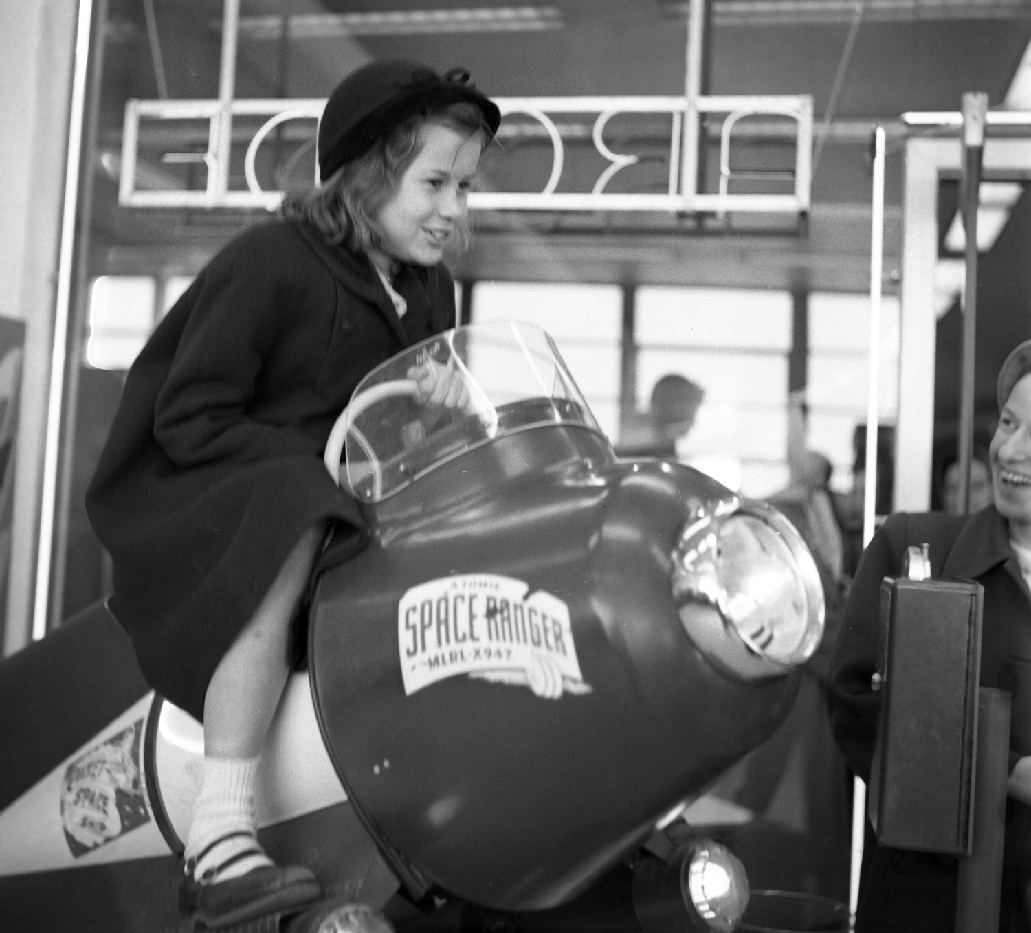 August 1952: One girl takes flight in the penny arcade. (Stewart Love/The Pittsburgh Press)