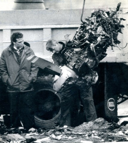 Members of the National Transportation Board Safety Board look over one of the engines of the plane that collided with the helicopter.