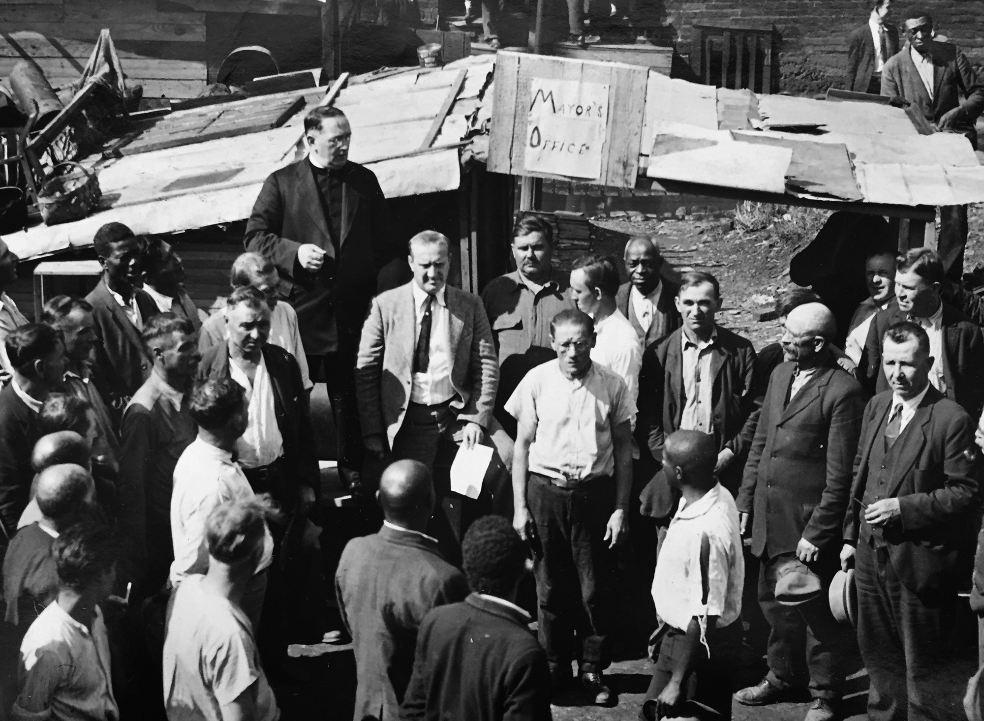 Father Cox rises above the crowd as the shantytown's mayor. (The Pittsburgh Press)