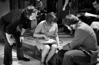 On the set of Mister Rogers' Neighborhood and reviewing a script are, left to right, Nick Tallo, studio floor manager; Diana Dean, associate producer and film producer; and Jim Seech, crew member.