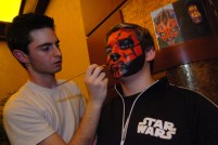 "George Tropster, left, a student at the Art Institute majoring in Industrial Design/Special Effects Makeup, paints Mike Cartier's, 13, from Carmichaels, face as ""Darth Maul"" at a Star Wars Premiere Party at Loews at the Waterfront in advance of the first showing of ""Star Wars: Episode III: Revenge of the Sith"" at 12:01 a.m. Thursday, May 19, 2005. (Alyssa Cwanger/Post-Gazette)"
