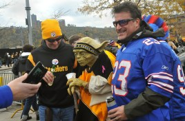"""Brian Rasbach, left, of Atlanta, Ga., and Jason Cataldo, right, from Durham, N.C., poses for photos with a Steelers-clad statue of Yoda from """"Star Wars"""" in the parking lot outside Heinz Field, Nov. 10, 2013. (Larry Roberts/Post-Gazette)"""
