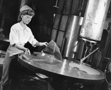 """The Clark Bar's core includes peanut butter and caramel mixed into a thick taffy. After the taffy was cooked, but before the other ingredients were added, it was poured on a giant griddle to cool. The original caption says it resembles a """"golden omelet."""" Once it became lukewarm, the taffy was ready for pulling. This worker scrapes off a batch as another begins to pour out. Picture taken March 21, 1948. (Pittsburgh Press)"""