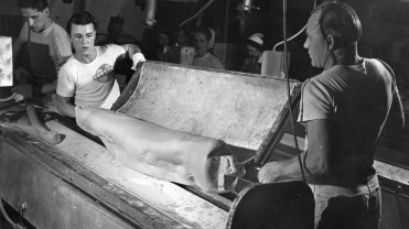 Workers added peanut butter and caramel to the taffy in order to make the Clark Bars' filling. A prepared batch weighed about 100 lb. and had to be carried to a spinning machine on a stretcher. Picture taken March 21, 1948. (Pittsburgh Press)