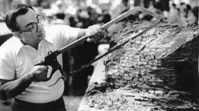 """Tony Murgid saws apart the """"Largest Candy Bar in the World,"""" which was about 15 ft. long and 20 in. thick. Pieces were handed out for Kennywood visitors to enjoy. Picture taken Aug. 14, 1981. (Pittsburgh Press)"""