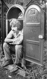 Ed Klinger of Bellevue gets out of the rain while waiting for a mail truck to arrive. Photo published June 27, 1977. (Pittsburgh Press)