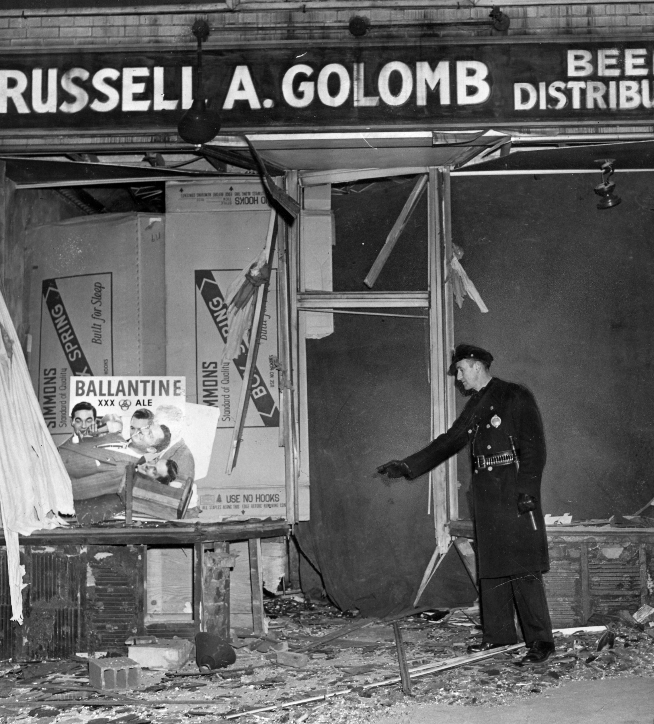 Police inspect Russell Golomb's bombed beer store. Three months prior, his father Ben's store was also attacked. Photo published Feb. 8, 1946. (Pittsburgh Press)