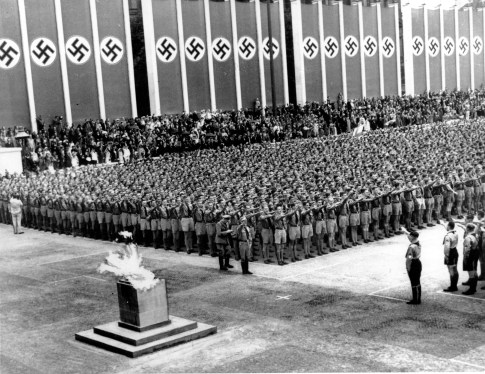 German Nazi soldiers line up at attention during the opening ceremonies of the Summer Olympic Games at the Lustgarten in Berlin, Germany on Aug. 1, 1936. The lighted Olympic torch is in the foreground. (Associated Press)