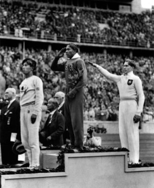 In this Aug. 11, 1936 file photo, Jesse Owens of the U.S., center, salutes during the presentation of his gold medal for the long jump, after defeating Nazi Germany's Lutz Long, right, during the 1936 Summer Olympics in Berlin. Naoto Tajima of Japan, left, placed third. (Associated Press)