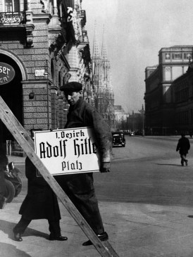"""A workmen in Vienna City square carries a name plate, on March 14, 1938, renaming a town square to """"Adolf Hitler Place."""" (Associated Press)"""