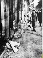 In this Nov. 10, 1938 file picture, a man with a broom prepares to clear up the broken window glass from a Jewish shop in Berlin, the day after Kristallnacht. (Associated Press)
