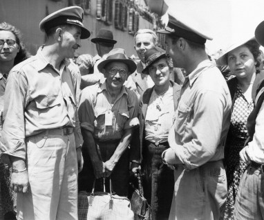 Merchant Mariners Lt. Herbert L. Parker, left, and ensign John Jay Yelcich, right, talk with some of the 984 European refugees on the pier in Naples, Italy on August 6, 1944. The refugees boarded transport ships, which took them to the United States. The group was selected after screening by a sub-committee of the Allied Control Commission, comprised of British and Americans, and the War Refugee Board. They arrived in the U.S. on August 4, and they were then taken to an emergency shelter prepared for them. (Associated Press)
