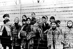 This file picture taken just after the liberation by the Soviet army in January, 1945 shows a group of children wearing concentration camp uniforms behind barbed wire fencing in the Auschwitz concentration camp. (Associated Press)