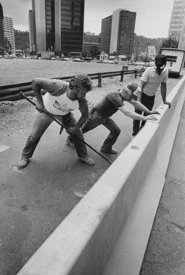 From left, John Hasenkoph of Brookline, Kenny Rudden of Whitehall and John Hunchar of Latroke set up concrete barriers ahead of construction for Fifth Avenue Place on Aug. 21, 1985. (Tony Tye/Post-Gazette)