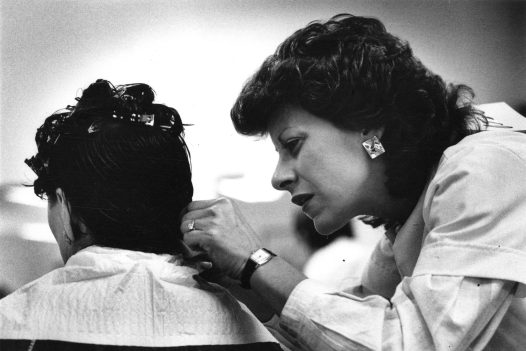 A student at Franco Beauty Academy styles her mother's hair for a final exam.