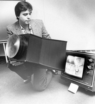 "Jim Thomason attaches a device which enlarges the image on a TV set, Feb. 3, 1982. Large screen TVs were prohibitely expensive for the average consumer at the time, but Thomason promoted his invention as being ""twice as bright and half the price."" (Anthony Kaminski/Pittsburgh Press)"