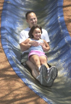 Roger Rosner of Shadyside rides down the concrete slide in the playground at Frick Park with his daughter Emma, 5, June 28, 2002. (Andy Starnes/Post-Gazette)